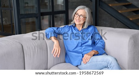 Mature smiling peaceful 60s middle age lady sitting on couch relaxing at home. Senior elder serene woman in glasses looking away thinking of positive vision, dreaming of future and enjoying wellbeing.