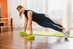 Mature sportive woman exercise at home floor mat, twist legs, using foam plastic bricks blocks, active retirement concept