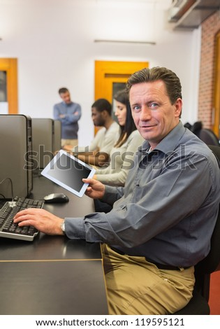 Mature student in computer class holding tablet pc in college