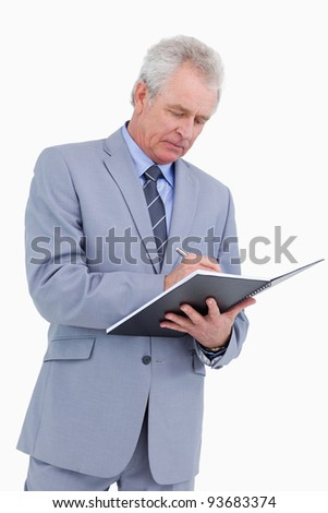 Mature tradesman taking notes against a white background