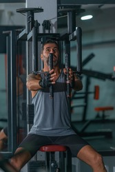 Mature trainer athlete working out chest muscles doing strength training exercises on gym benchpress equipment.