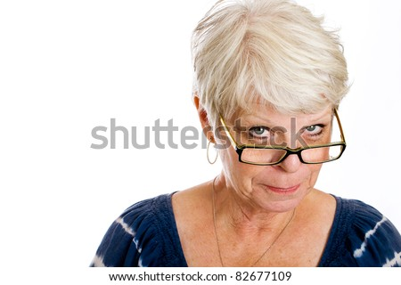 Mature, white haired woman with a skeptical expression on her face while looking over the rim of her glasses.
