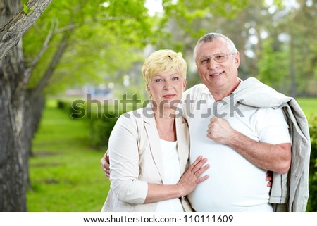 Mature woman and her husband looking at camera while having rest outside
