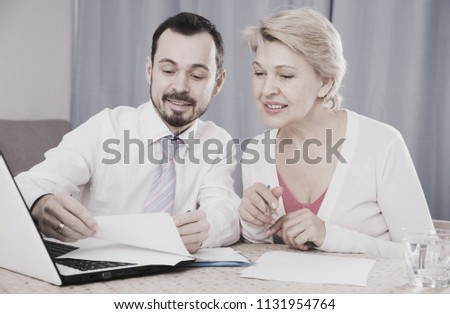 Mature woman and smiling sales manager discussing documents before signing #1131954764