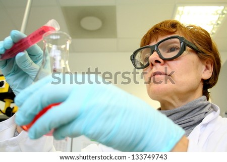 Mature woman as a research assistant in laboratory, soft focus
