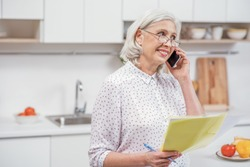 Mature woman calling utility service at home
