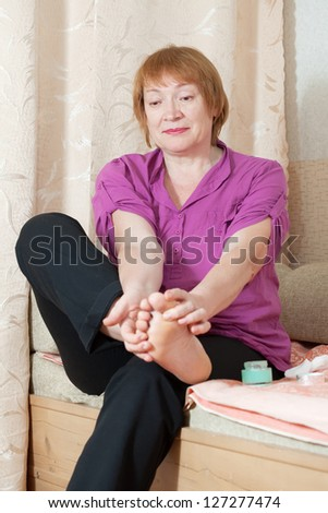 Mature woman caring for the nails on your feet