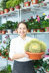 mature woman chooses cactus at flower store
