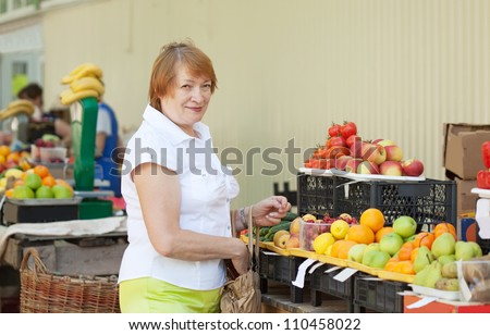 Mature woman  chooses fruits and vegetables at  market
