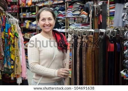 Mature woman  chooses  strap at fashionable shop - stock photo