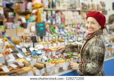 Mature woman chooses sweets at shop
