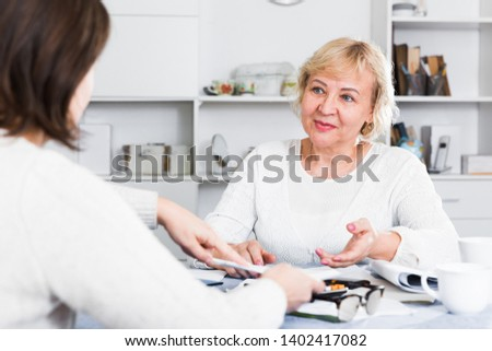 Mature woman consults with a financial adviser for the proper conduct of home accounting #1402417082