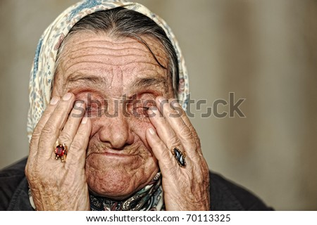 Mature woman crying with hands on her face - stock photo