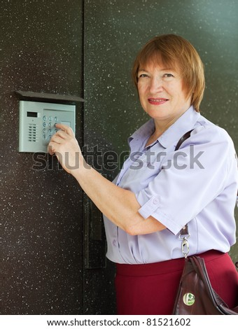 Mature woman dialing an intercom to enter a building