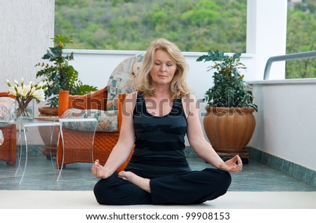 mature woman doing lotus yoga position on her home balcony
