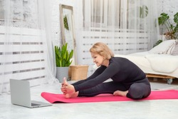 Mature woman doing sports at home on a Mat, healthy lifestyle concept.