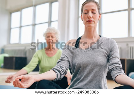 Mature woman doing yoga with senior female in background. Women sitting in lotus pose while mediating in yoga class