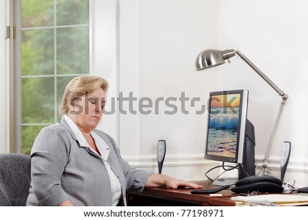 Mature woman dozes off at her desk. Clipping path for monitor