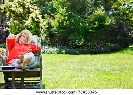 Mature woman dozing off in a sunny garden chair