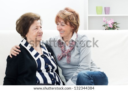 Mature woman embracing her mother and sitting on the couch in the living room.