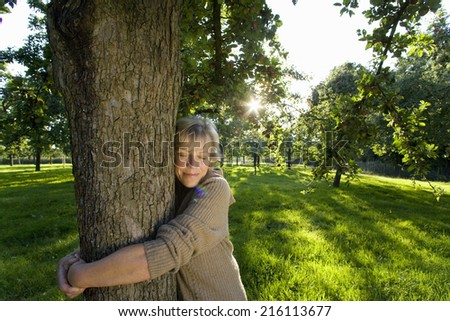 Mature woman embracing tree, eyes closed (lens flare)