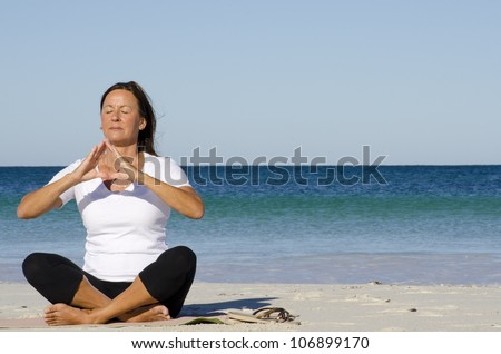 Mature woman exercising at beach, keeping healthy and fit with yoga and pilates, isolated with ocean and blue sky as background and copy space.