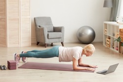 Mature woman exercising on the floor in front of laptop in the living room at home