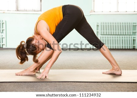 Mature woman exercising yoga in a gym - stock photo