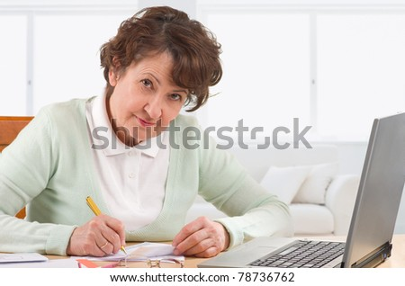 Mature woman fill finance invoice at home