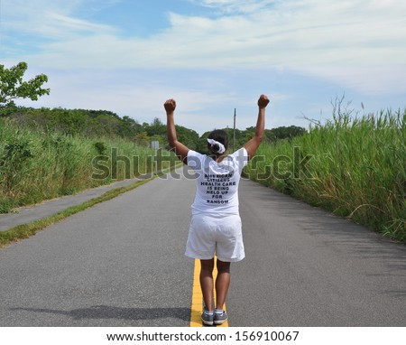 Mature Woman Fists Raised American Healthcare for Ransom on Tee Shirt Back to Camera Standing on Street Yellow Traffic Line