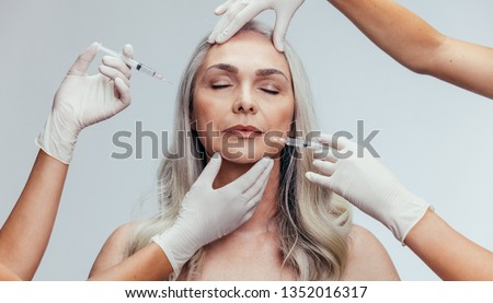 Mature woman getting anti wrinkles aesthetic treatment on face by cosmetic doctors. Senior female getting injection on her face by beauticians over grey background. Photo stock ©