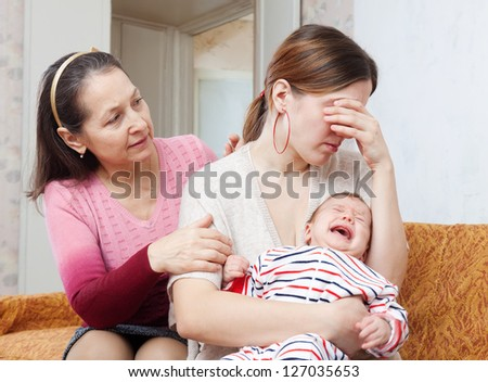 Mature woman gives solace to crying adult daughter with baby at home