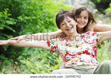 Mature woman has happy time with her daughter in nature