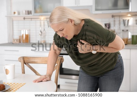 Mature woman having heart attack in kitchen
