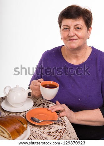 Mature woman having tea on a white background
