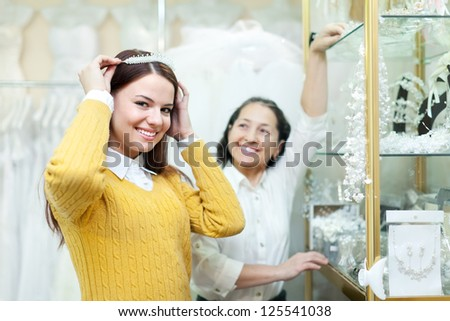 Mature woman helps the bride in choosing bridal diadem at wedding store. Focus on girl