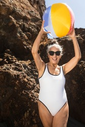 Mature woman holding a beach ball while in a swimsuit