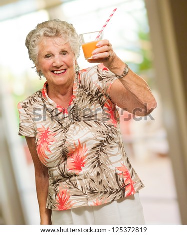 Mature Woman Holding Juice Glass, Indoors