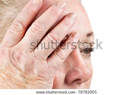 Mature woman holds her head in pain. Focus on fingers.