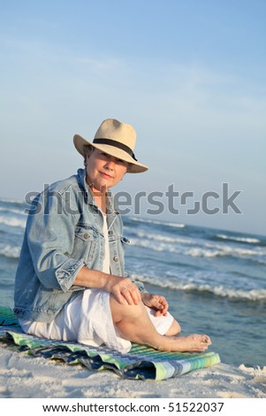 Mature woman in a Panama hat, seated at the beach at sunset. #51522037