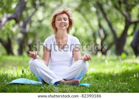 Mature woman in a park yoga
