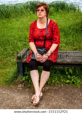 Mature woman in a red dress resting by the lake sitting on a bench
