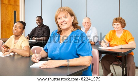 Mature woman in college, among a group of other adult students.   Banner orientation.
