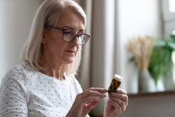 Mature woman in glasses hold bottle with pills read medicine instruction on packaging before take meds, senior female retiree in spectacles thinking of medication treatment, elderly healthcare concept