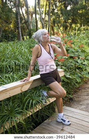 Mature woman in her 50s in workout clothes drinking a bottle of water, standing on wooden bridge in park