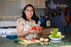 Mature woman in kitchen choosing vegetables to cook - Hispanic mom smiling cooking fresh organic salad in her kitchen