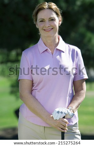 Mature woman, in pink polo shirt and golf glove, standing on golf course, leaning on golf club, smiling, front view, portrait