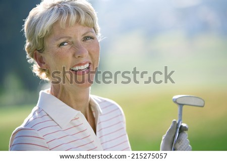 Mature woman in striped polo shirt and golf glove standing on golf course, holding putter, laughing, close-up, portrait
