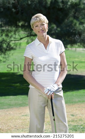 Mature woman, in striped short-sleeved shirt and golf glove, standing on golf course, leaning on golf club, smiling, front view, portrait