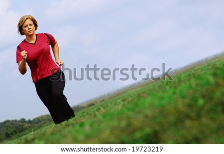 Mature woman jogging in a big summer field.